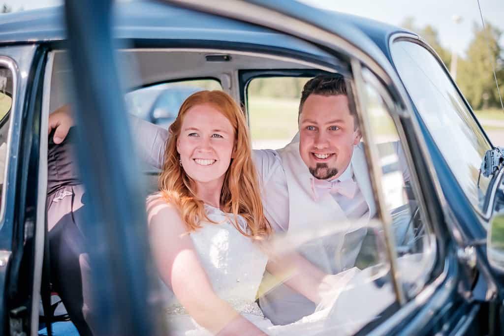 Ett bröllopspar i en blå folkvagn