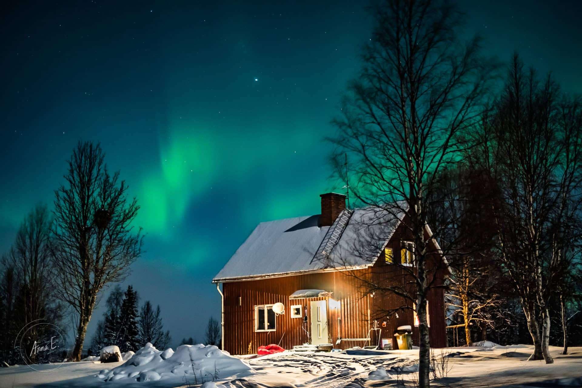 En månskensbelyst röd stuga i snön med norrsken - fotografera norrsken