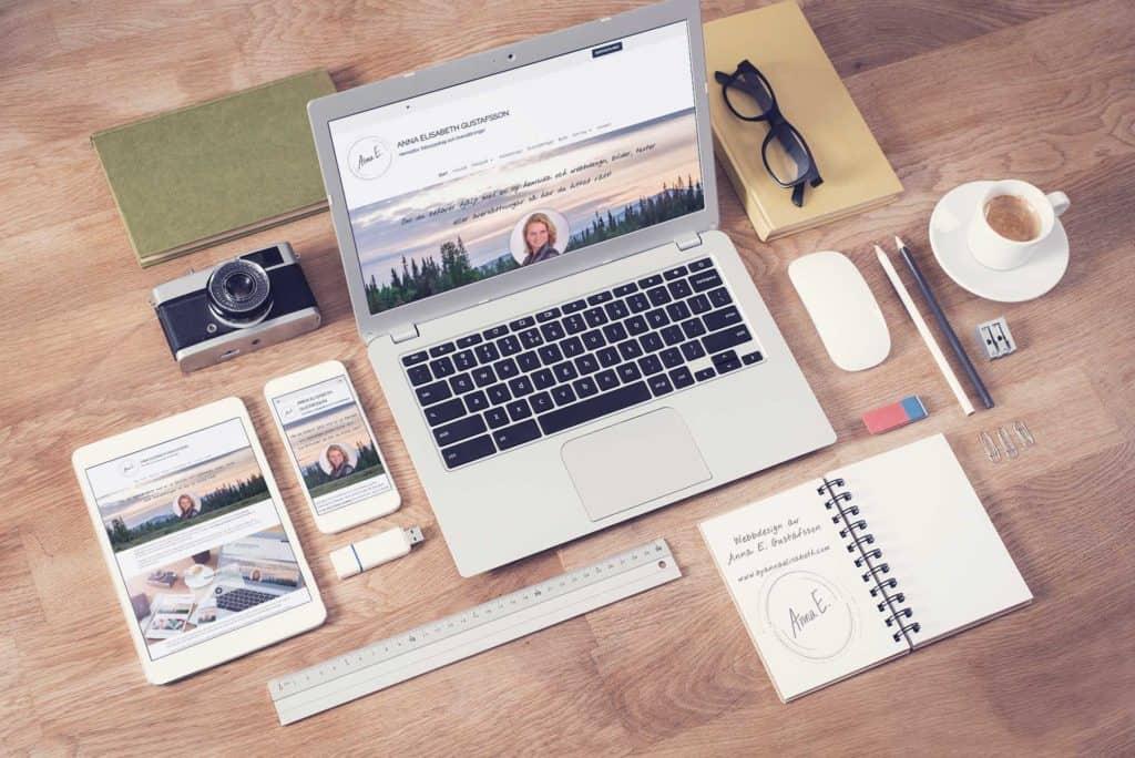 En arbetsplats som visar en responsiv hemsida och ett block där det står webbdesign byannaelisabeth