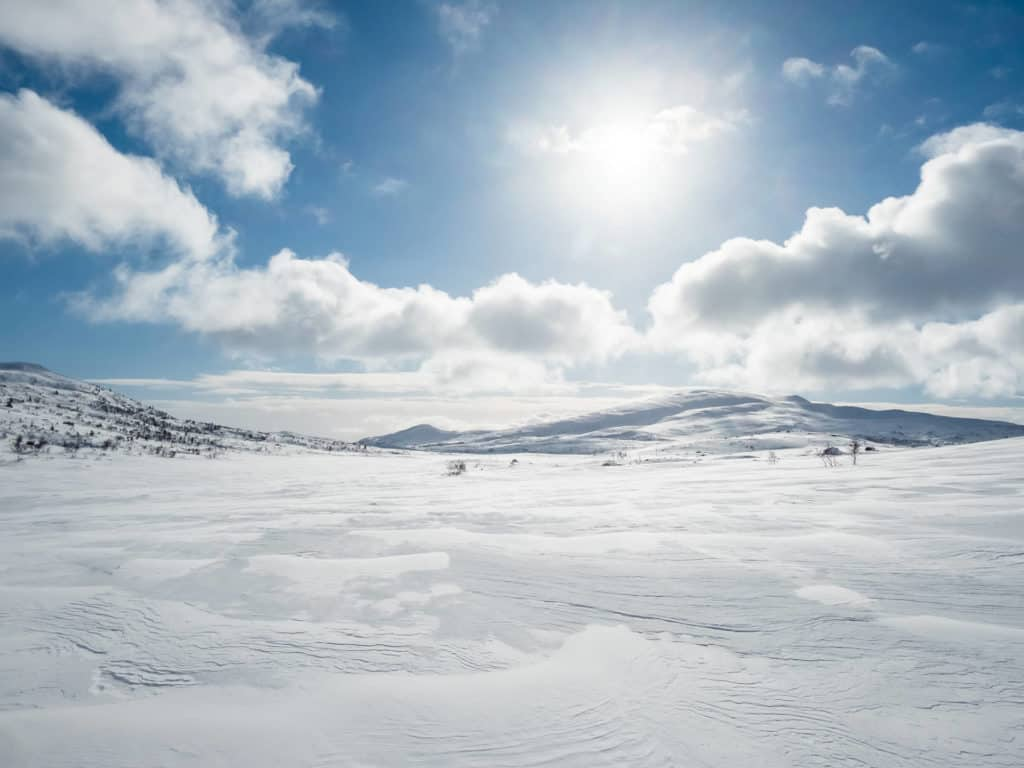 Njaarke fjällen som badar i vårens solljus och en blå himmel med några moln